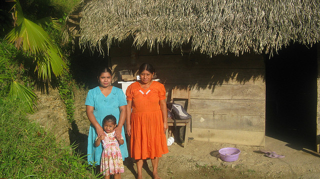 Mother & daughters in front of typical thatch style home.